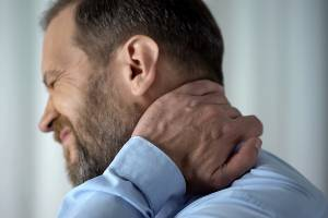 man struggling with neck pain