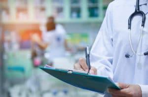 Doctor writing a medical prescription in hospital