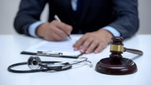 Judge signing wrongful death claim, banging gavel near stethoscope