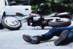 Victim of a motorbike accident lying on the street unconscious