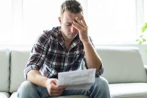 An Austin, TX, man feeling stressed while opening bills from his car accident.